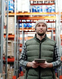 A man with a notepad standing in a warehouse